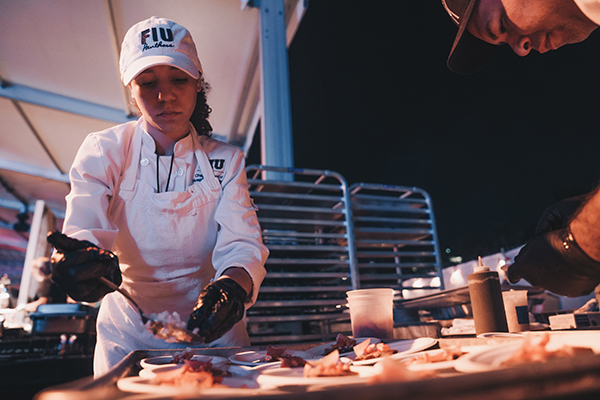 An FIU student preparing food at the SOBE food and wine festival